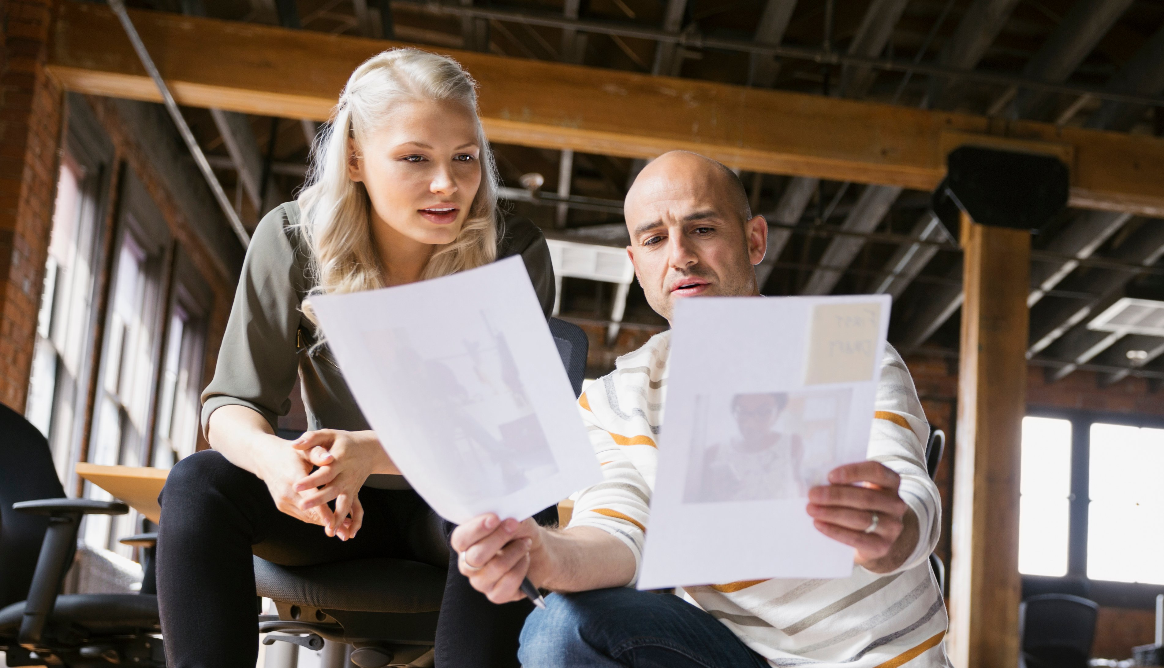 Male and female business people kneeling on the floor at their office with papers scattered around, reviewing proofs