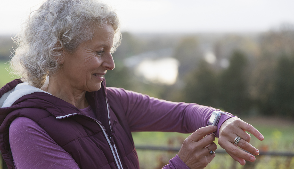 Active senior woman exercising, using fitness tracker smart watch