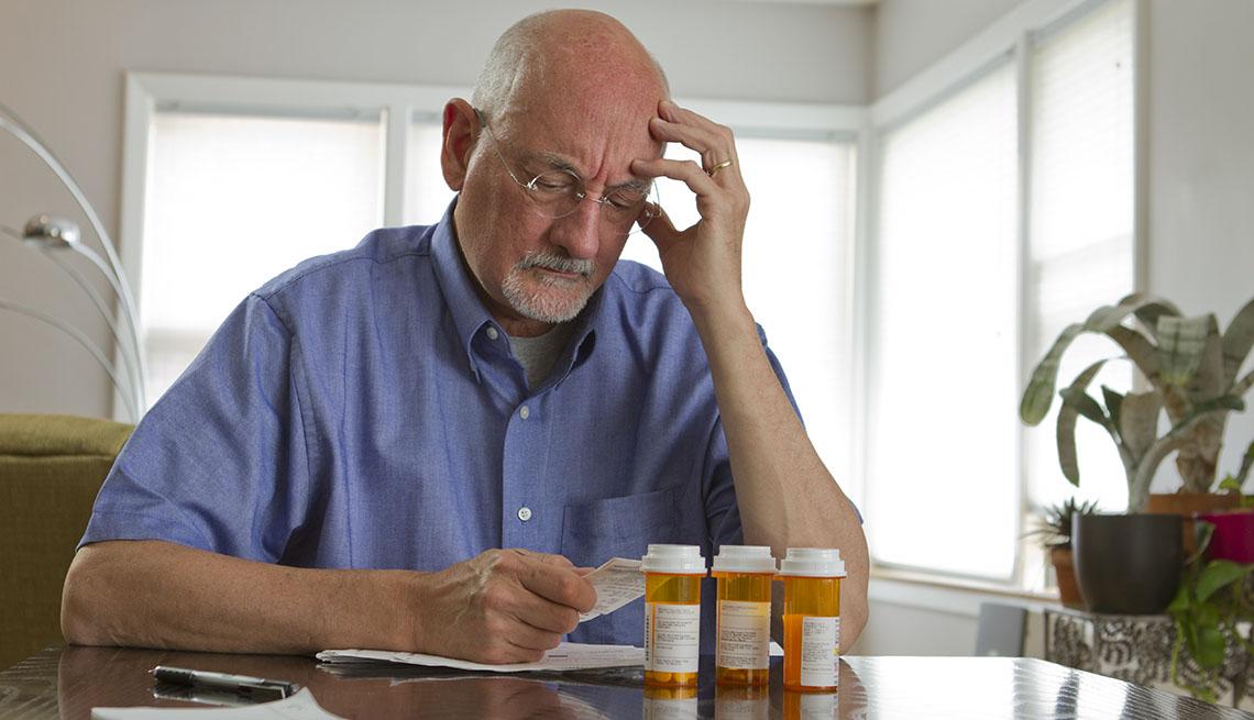 Older man at desk with prescription bottles