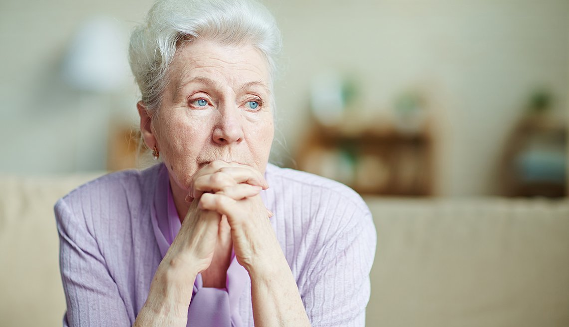 Woman with hands clasped by chin looking worried