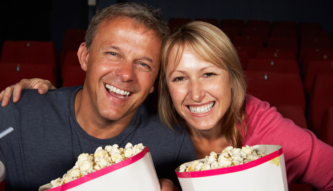 Mature couple eating popcorn at the movies