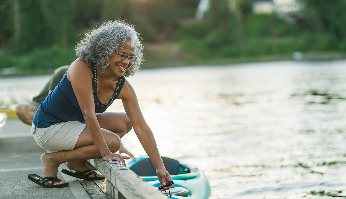 Woman on a pier putting kayak in the water