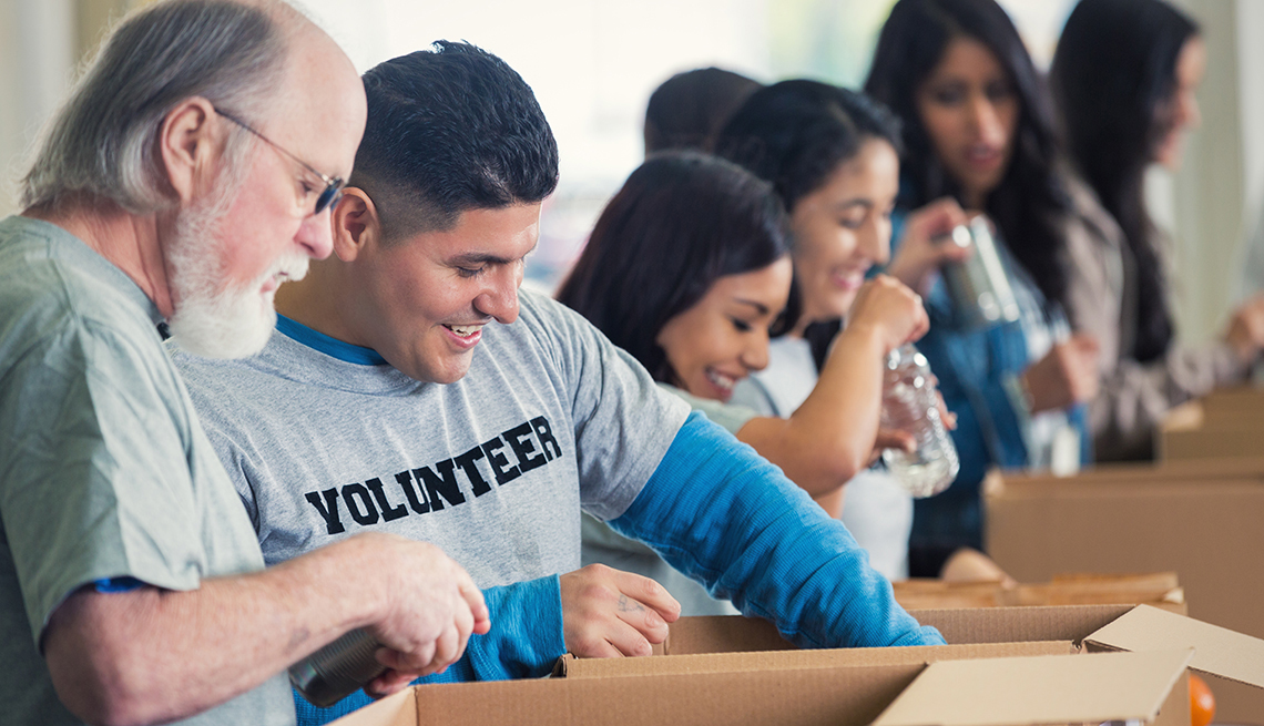 A group of volunteers packing boxes at a food bank