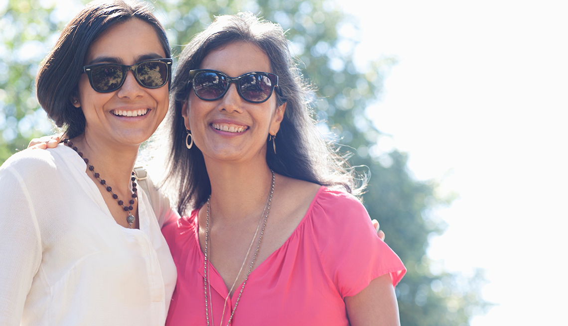 Smiling mother and daughter posing outdoors wearing sunglasses