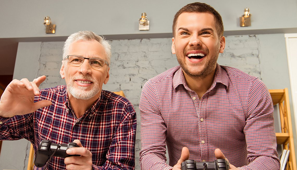 Older man and younger man playing a video game together at home