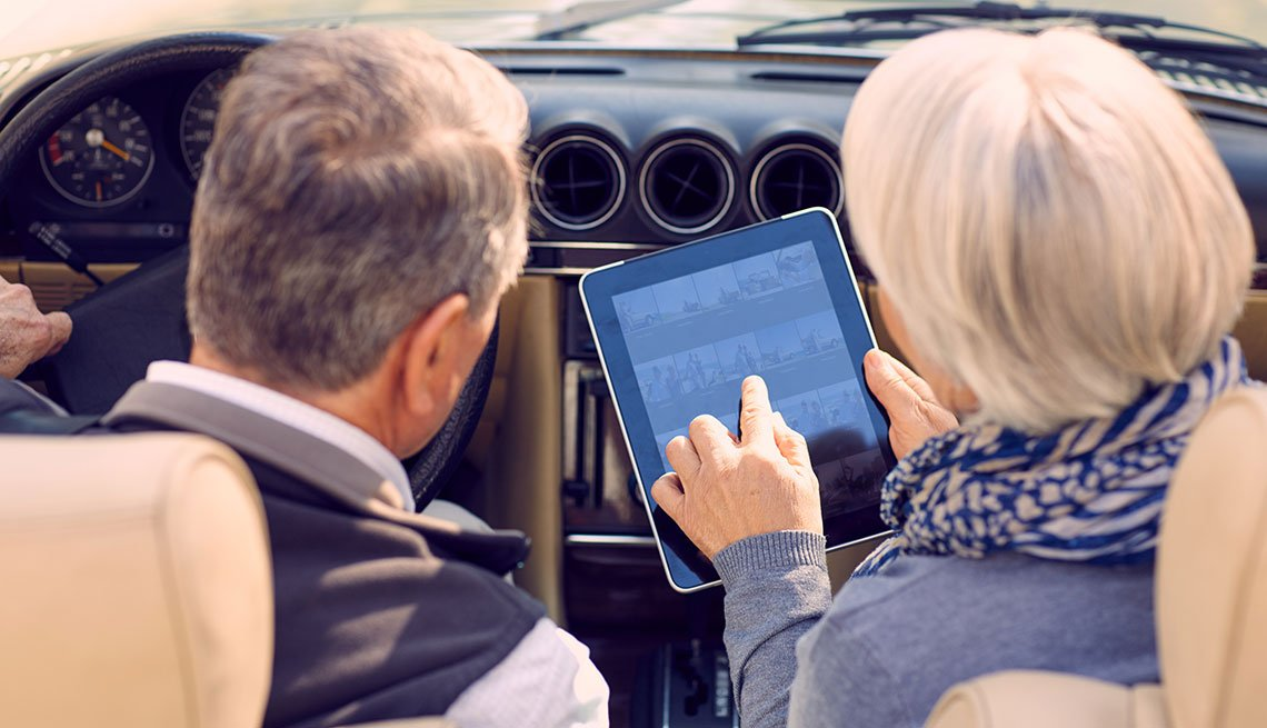 Mature couple in car using tablet