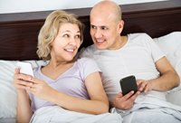 mature couple reading with smartphones in bedroom interior