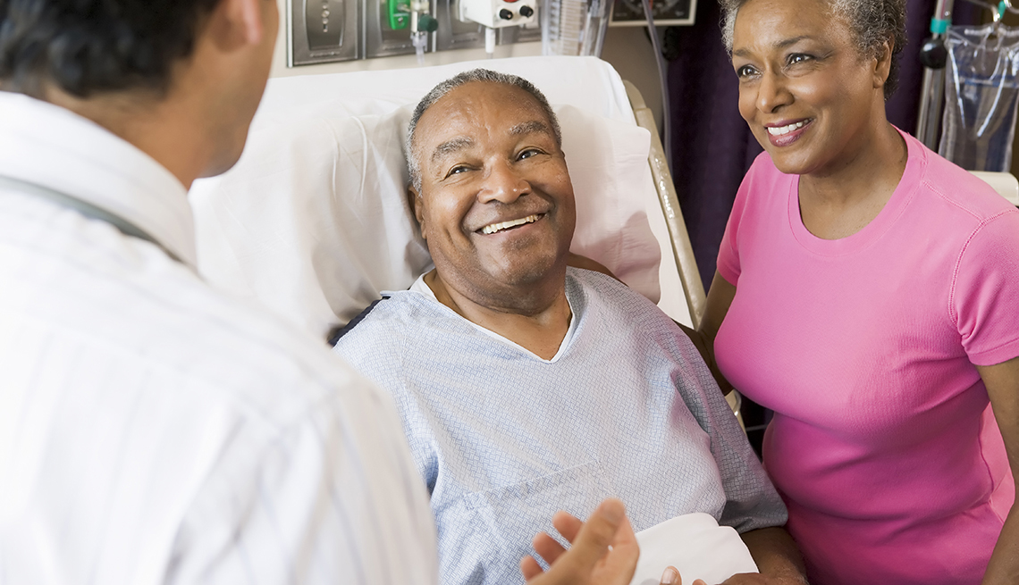 Senior couple talking with primary care doctor, smiling