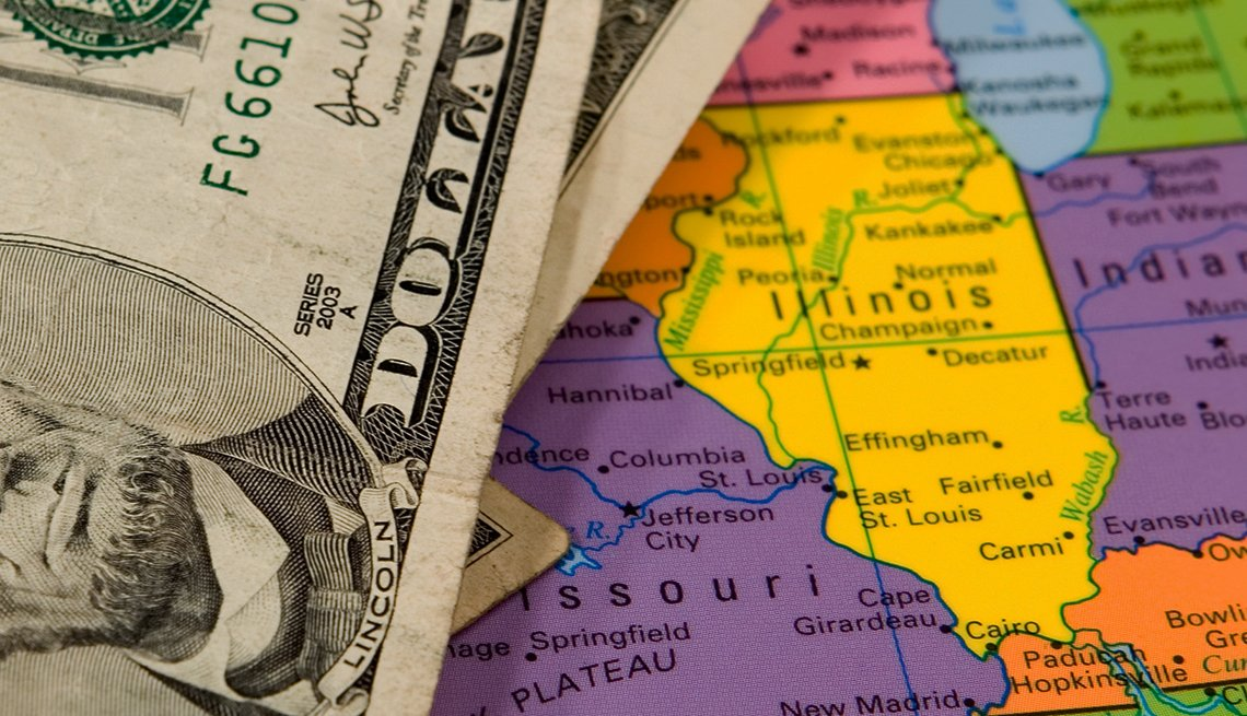 Five dollar bill on top of a colorful united states map