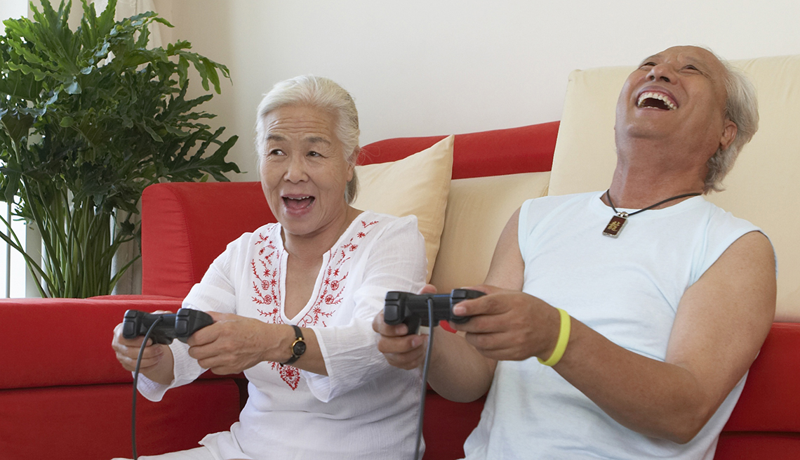 Couple sits on the floor, each holding a video game controller and laughing