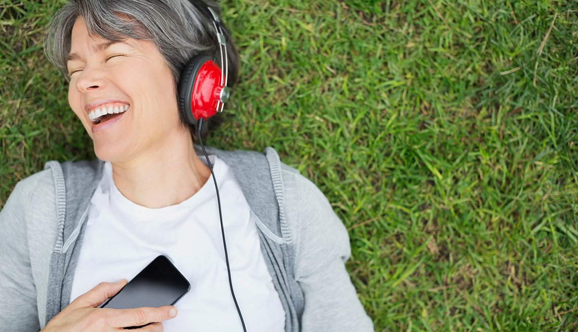 Happy woman listening to music at park