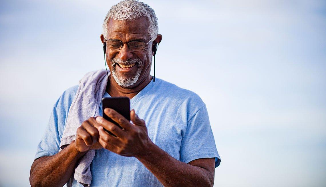 Black Man using smartphone on mountain trai