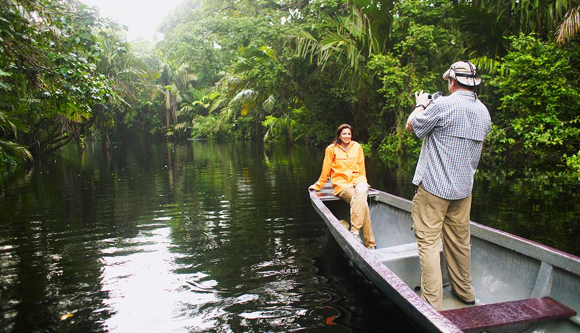 Hombre tomando foto a una mujer mientras navegan en una balsa