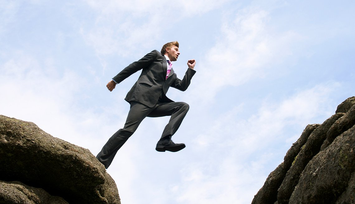 Man in suit leaps over crevice