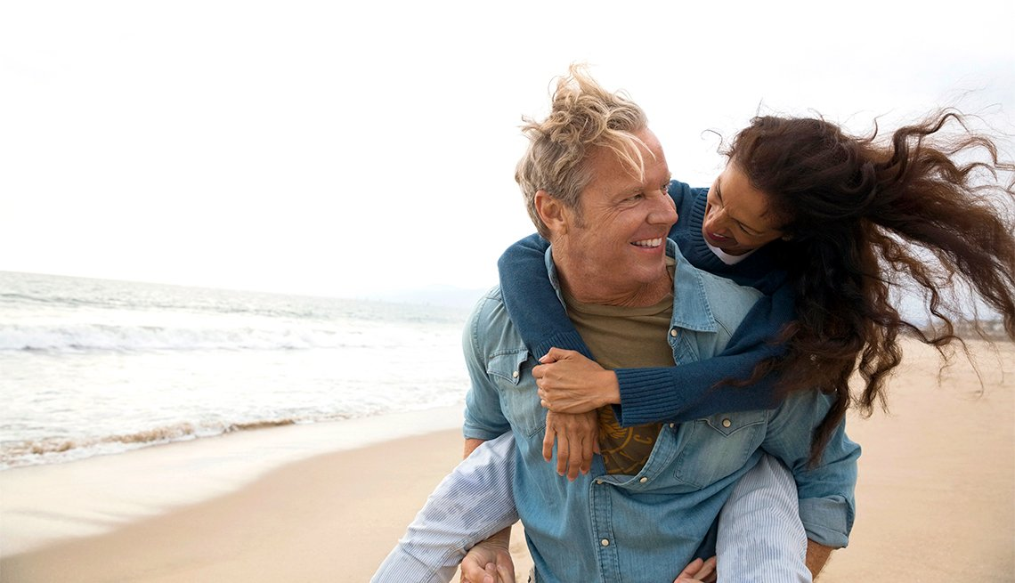 Playful couple piggybacking on beach
