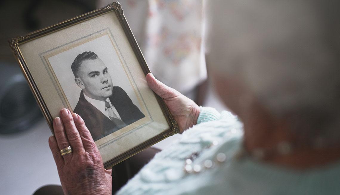 Mujer mayor sosteniendo un retrato
