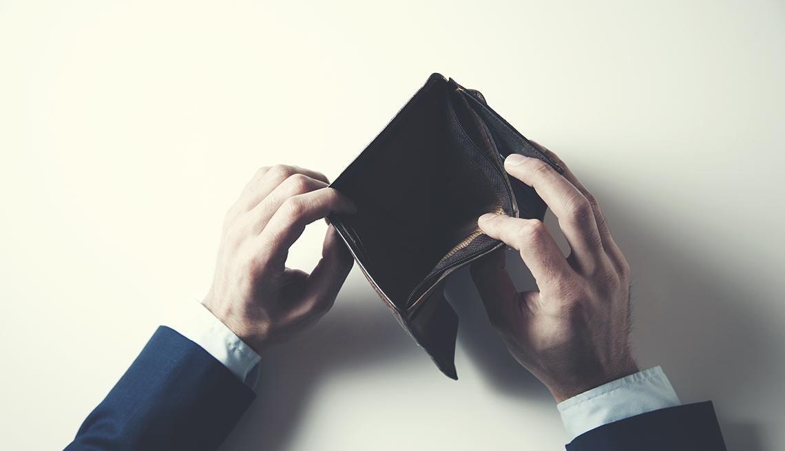 Manos viendo una billetera de hombre de cuero vacía
