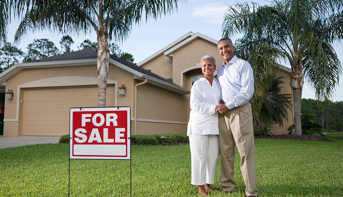 Pareja mayor frente a una casa con un letrero de se vende