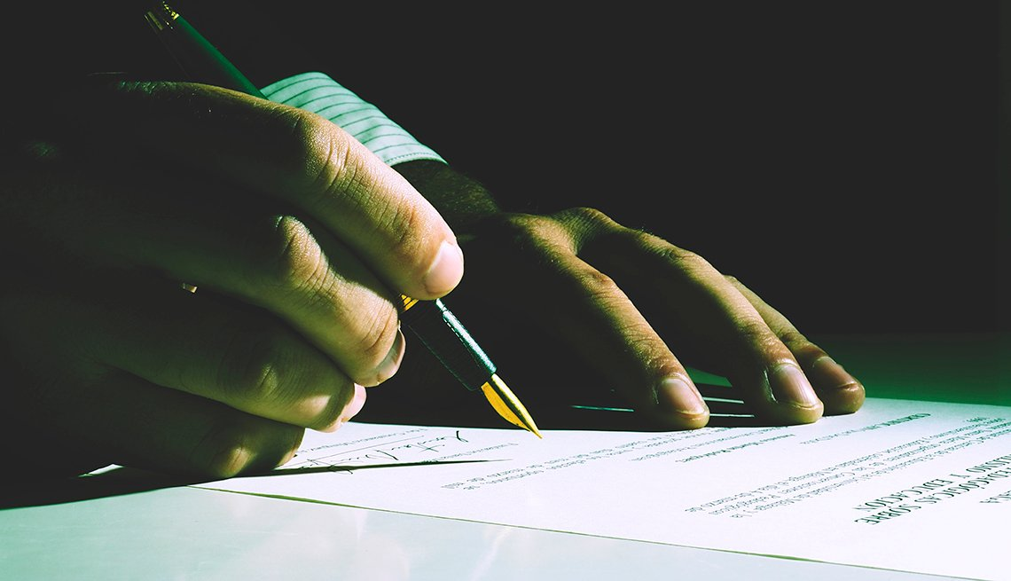 Person signing papers with dark background