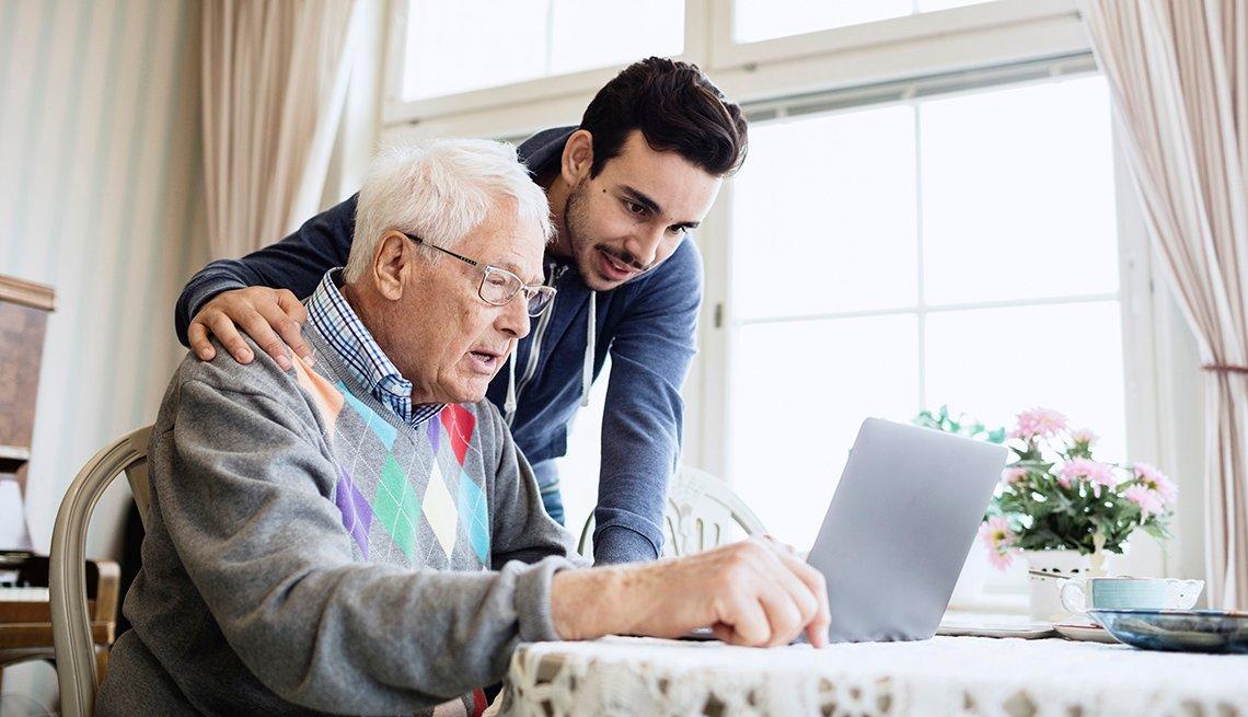 Hombre mayor frente a un computador portátil y hombre joven a su lado