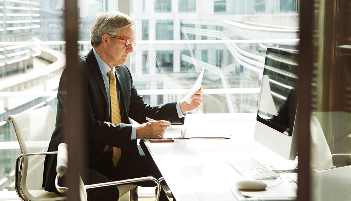 man looking at a piece of paper in front of a computer