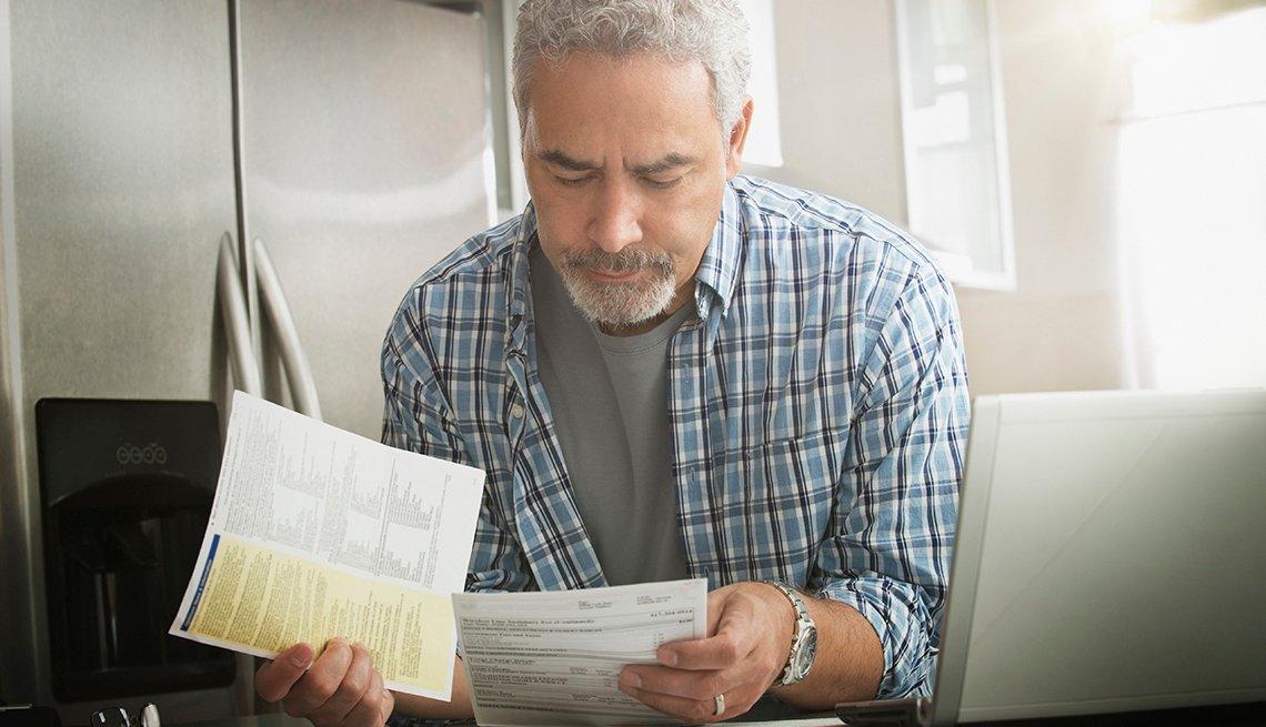 Hombre con cara de preocupación viendo facturas en una cocina