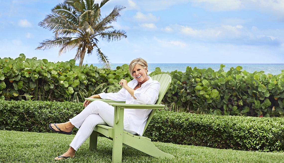 Suze Orman sentada en una silla con una playa al fondo