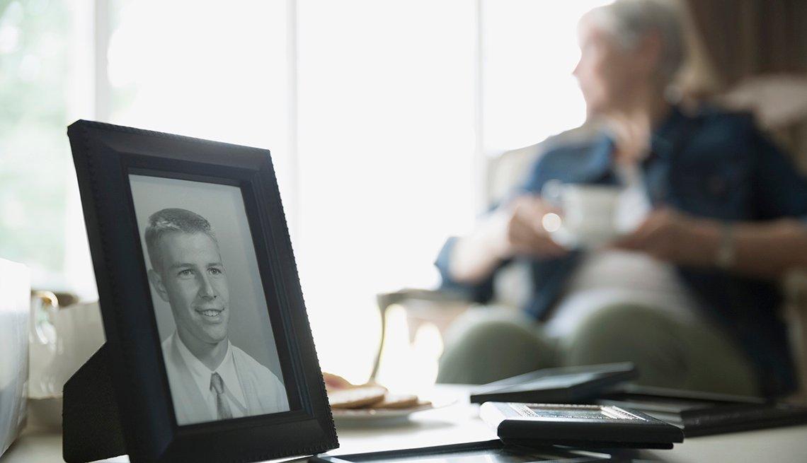 Retrato de un hombre sobre una mesa y una mujer mayor al fondo.