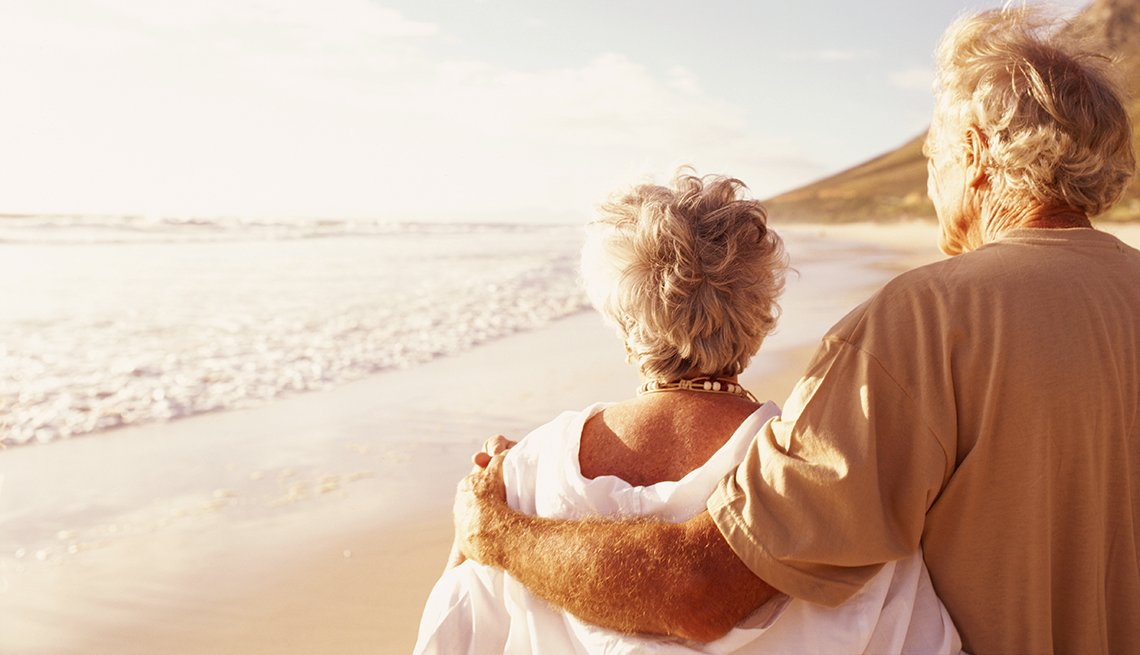 mature retired couple walking on the beach during sunset