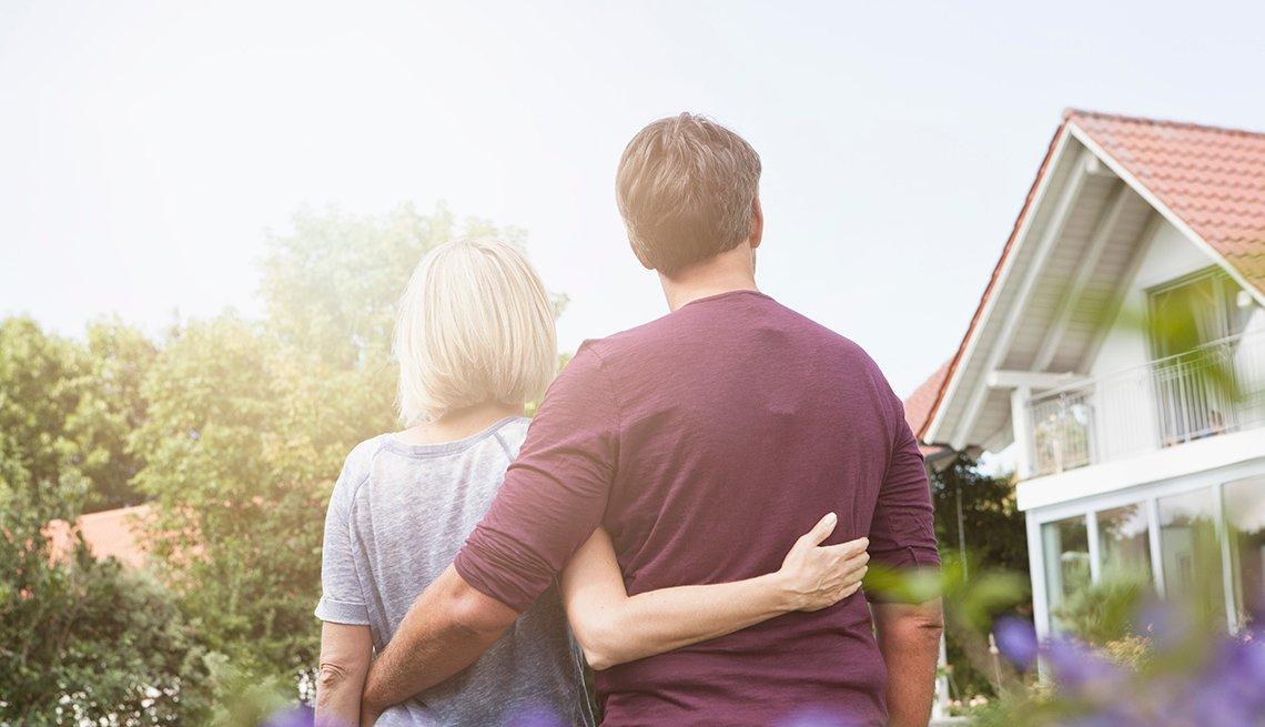 Pareja mayor abrazados y viendo una casa.