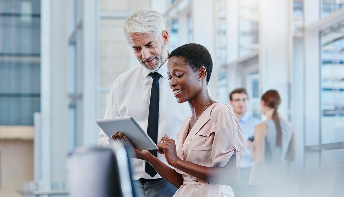 Hombre al lado de una mujer que mira una tableta