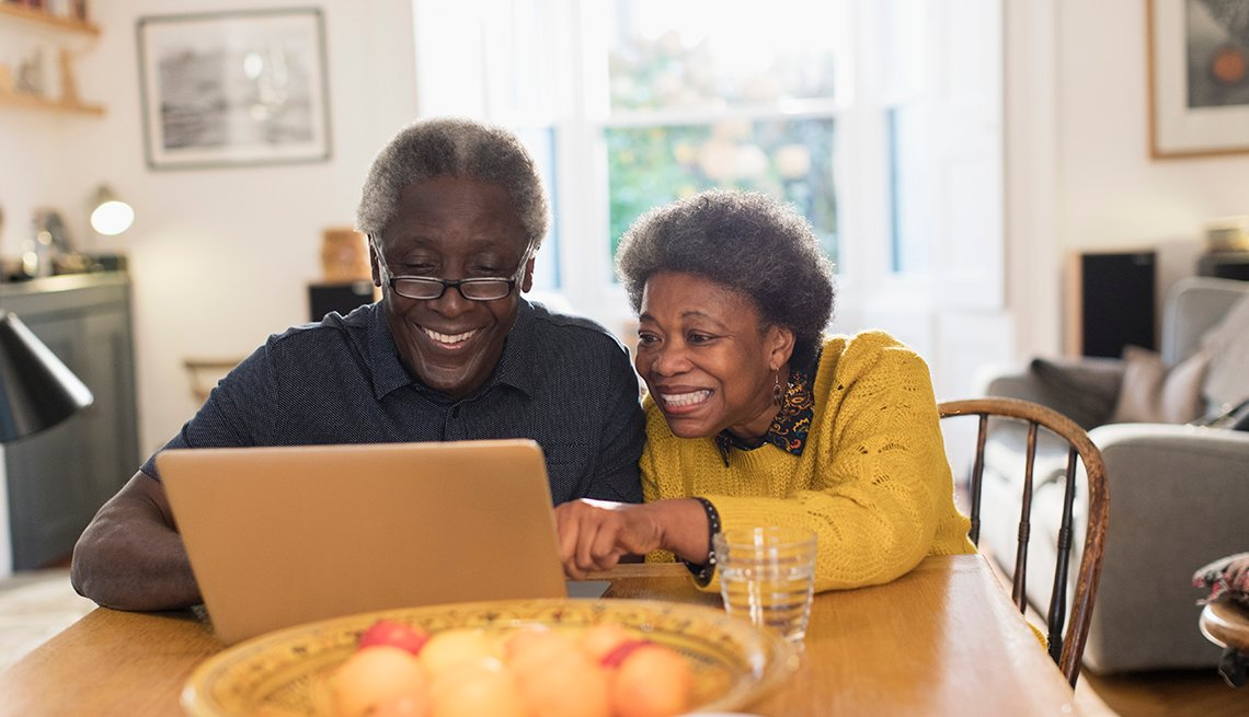 Mature couple smiling and looking at a laptop together