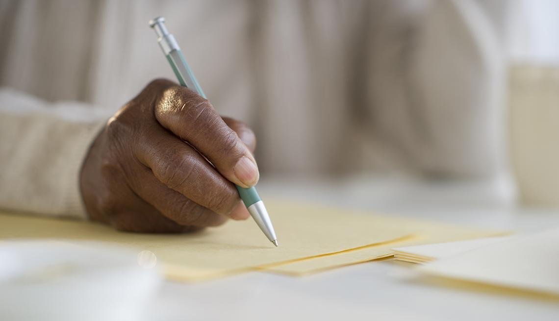 Mano escribiendo en una hoja