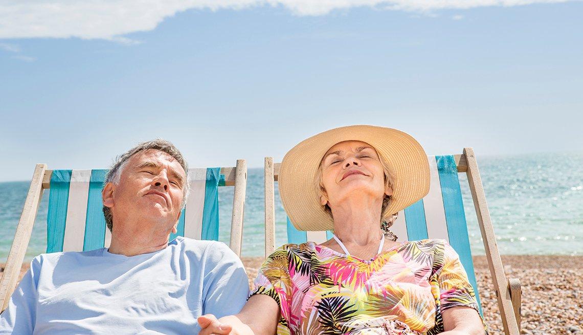 Pareja mayor tomando el sol sentados en una playa.