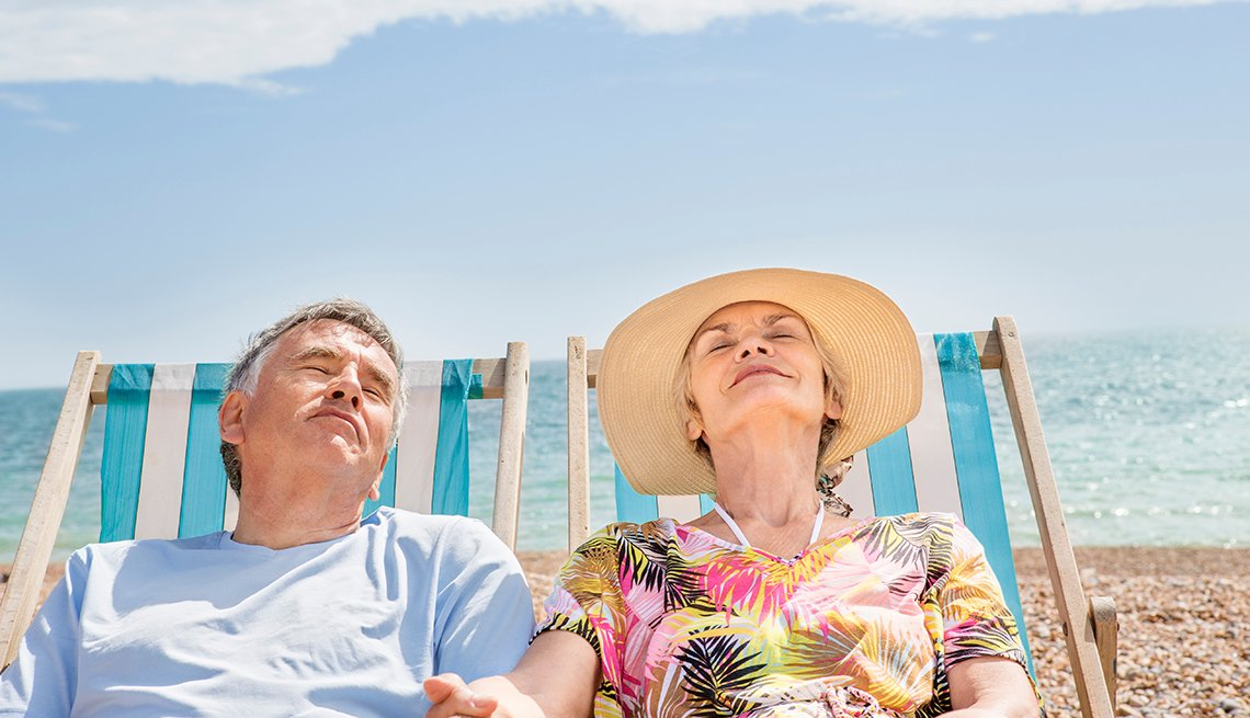 Couple in beach chairs, holding hands, smiling