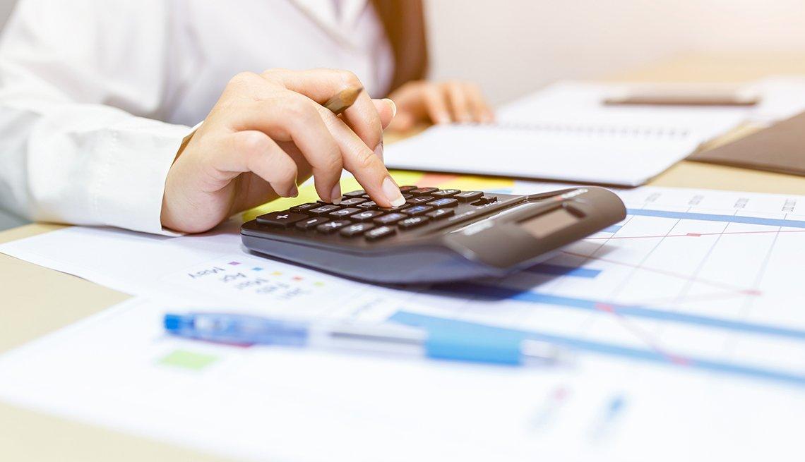 Manos de una mujer sobre una calculadora y papeles en un escritorio.