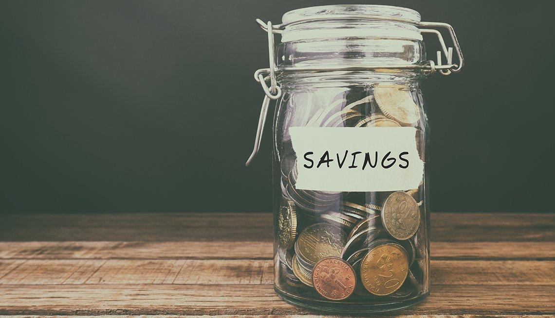 Jarro con tapa a presión lleno de monedas y el letrero ahorros en inglés