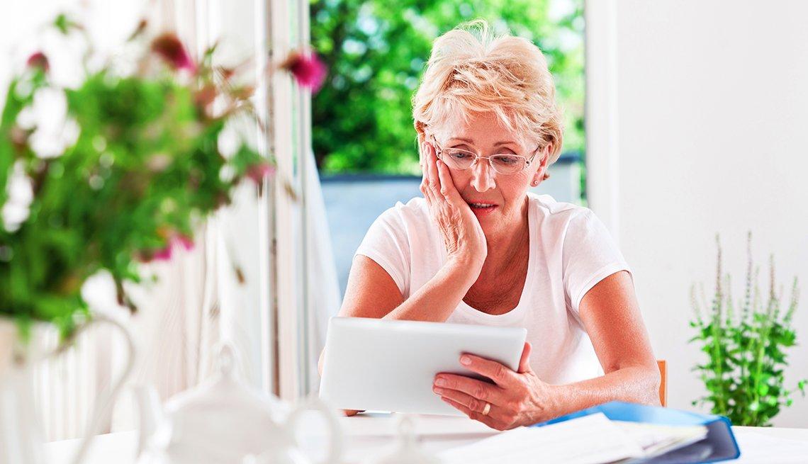Mujer sentada en una mesa de su casa, con cara de preocupación y sosteniendo una tableta