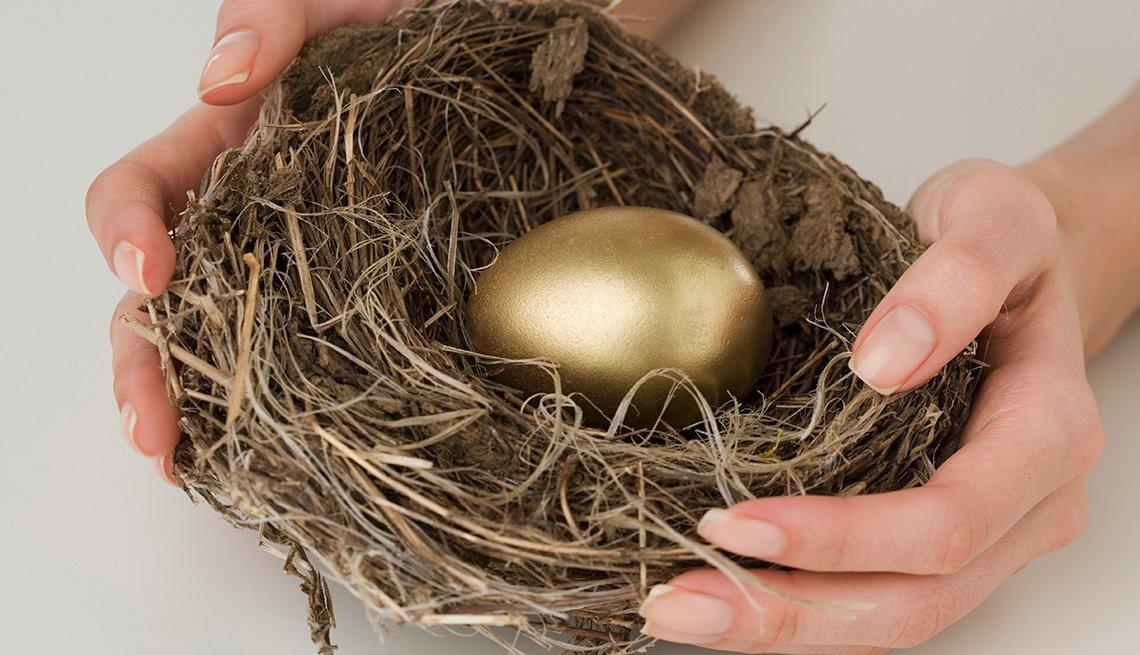 Manos sosteniendo un nido con un huevo de oro