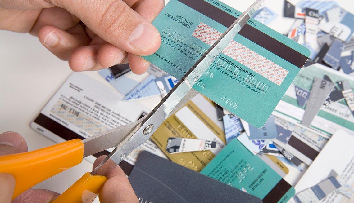 Persona cortando tarjetas de crédito