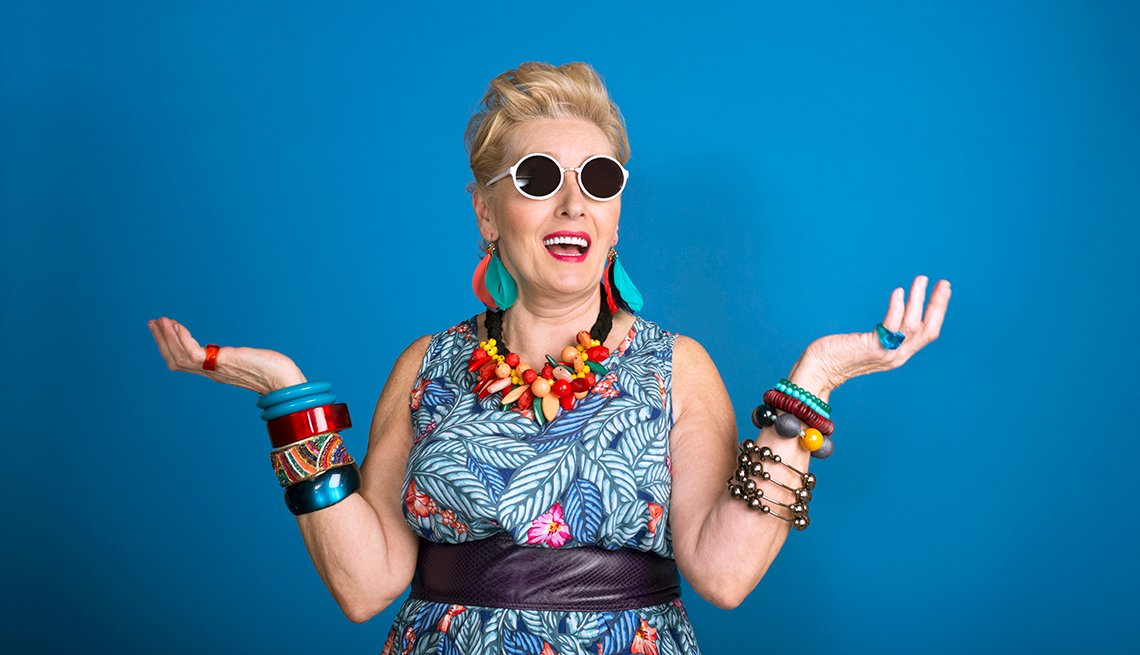 Blue background with creative, colorful mature woman standing in front of it, wearing sunglasses