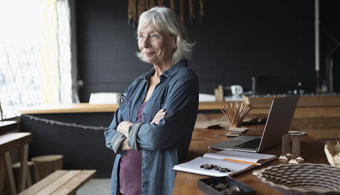 Mujer mayor parada frente a una computadora