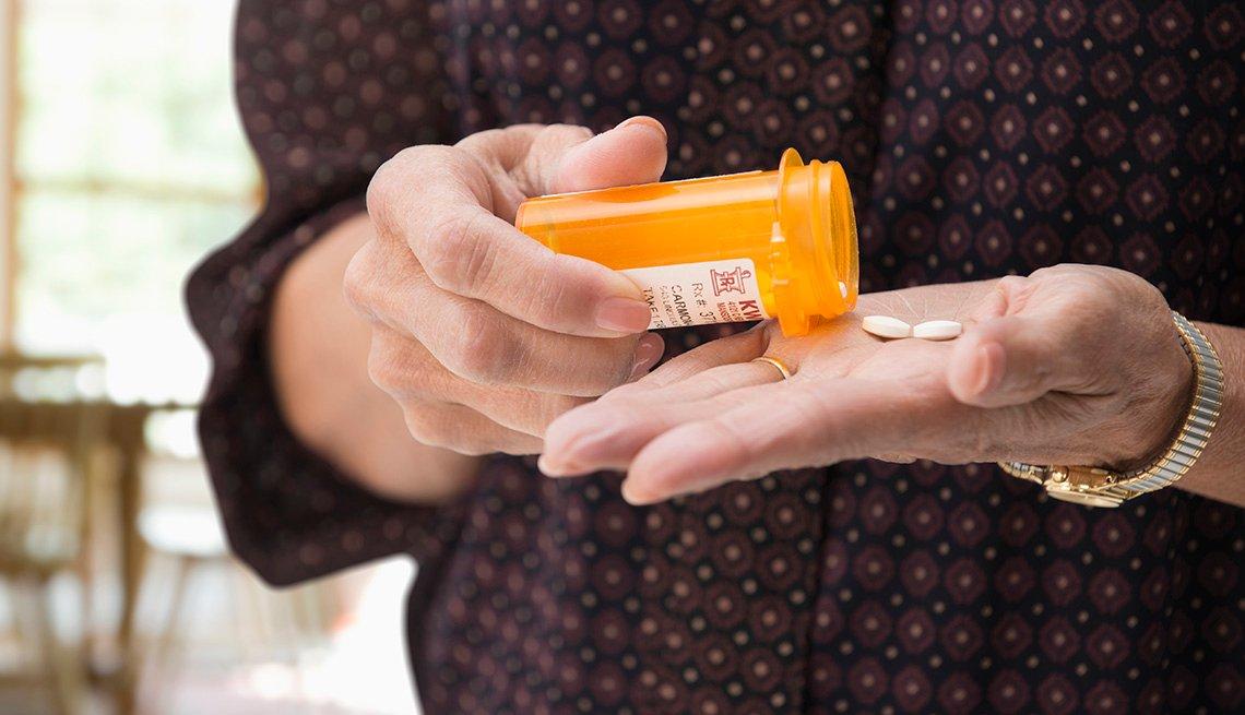 Mujer mayor con un tarro con pastillas en la mano.