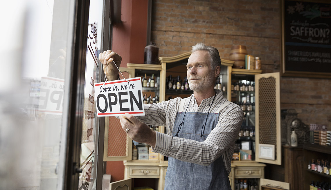 Hombre en una tienda de especias sostiene un letrero en inglés de 'Entre, está abierto'.