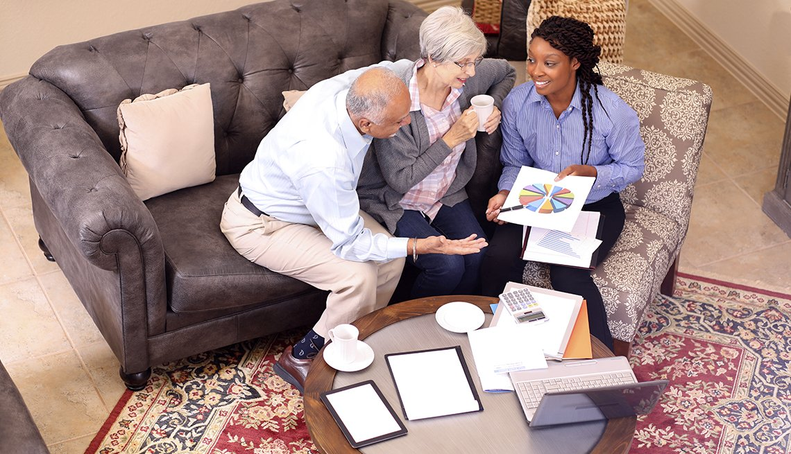 couple meeting with financial advisor in their living room
