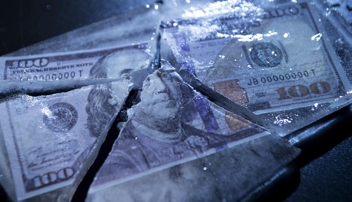 Billetes de 100 dólares congelados y partidos.