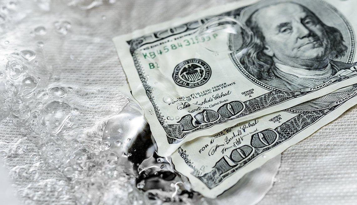 Dos billetes de 100 dólares que se van por un desagüe.