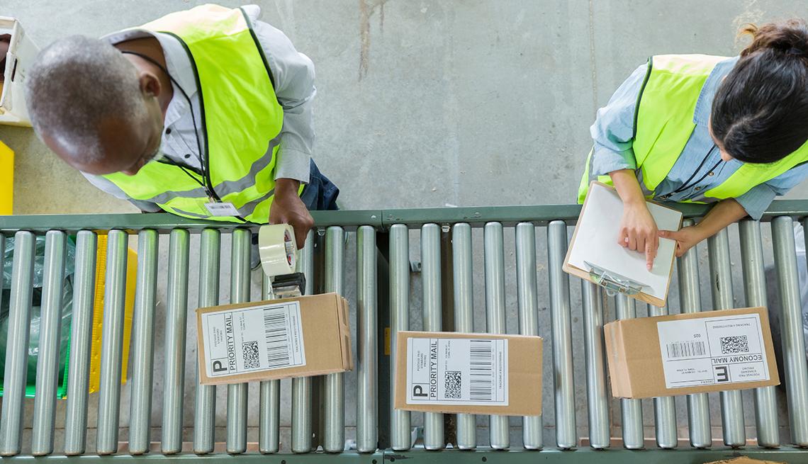 Operarios en una fábrica frente a un riel que pasa paquetes.