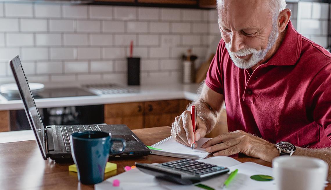 Persona mayor en una cocina mientras hace cuentas en una mesa y un computador portátil.