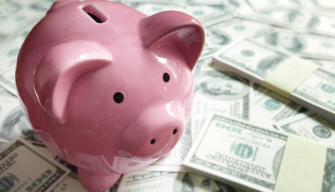 Alcancía rosada en forma de cerdito encima de fajos de dólares.